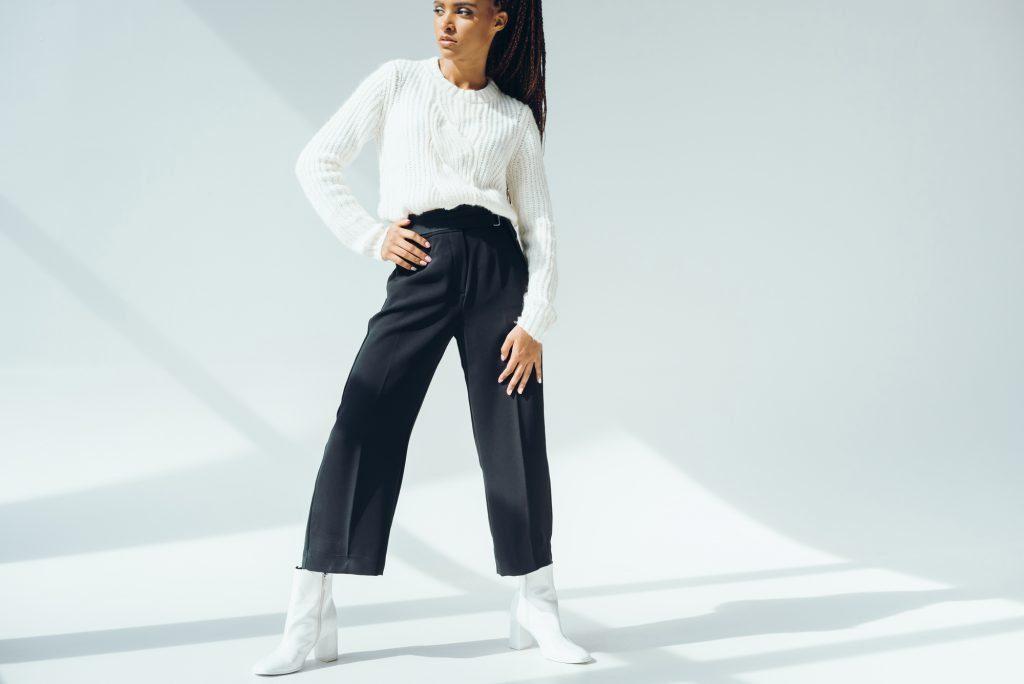 African-american lady in white sweater, black wide-leg pants, and white ankle boots. #widelegpants #wideleg #widelegjeans #denim #palazzo #croppedwideleg #womensfashion