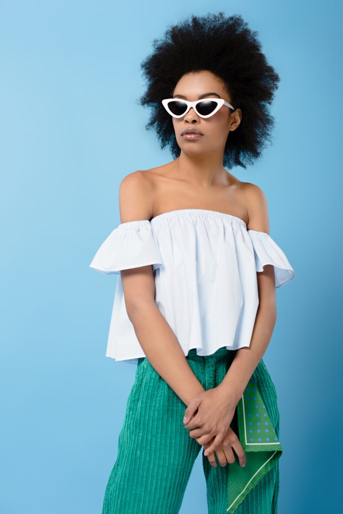 African-american woman with off the shoulder white top, white rimmed sunglasses, green wide leg pants. #widelegpants #wideleg #widelegjeans #denim #palazzo #croppedwideleg #womensfashion