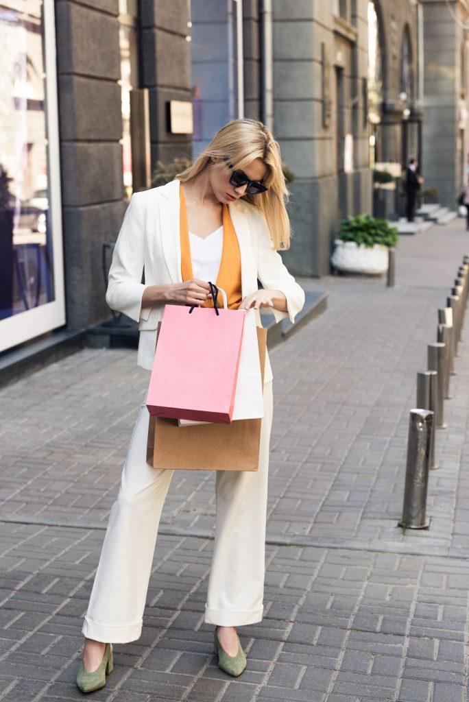 Caucasian lady wearing white wide leg pant suit, yellow scarf, carrying shopping bags, looking down in bag. #widelegpants #wideleg #widelegjeans #denim #palazzo #croppedwideleg #womensfashion