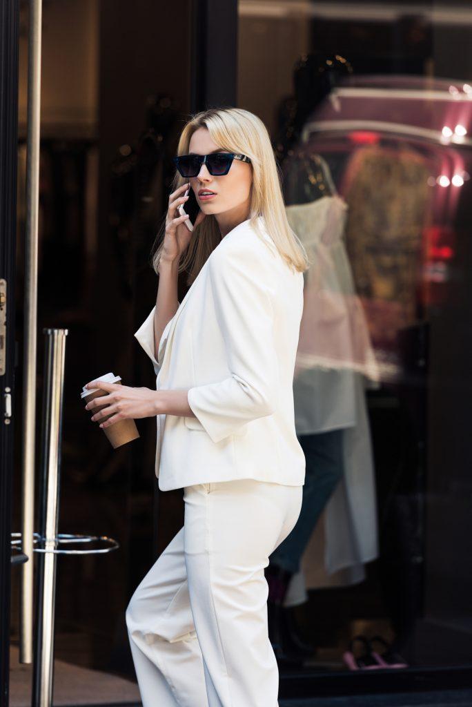 Caucasian women white pant suit black sunglasses carrying coffee one hand cell phone other hand. #widelegpants #wideleg #widelegjeans #denim #palazzo #croppedwideleg #womensfashion