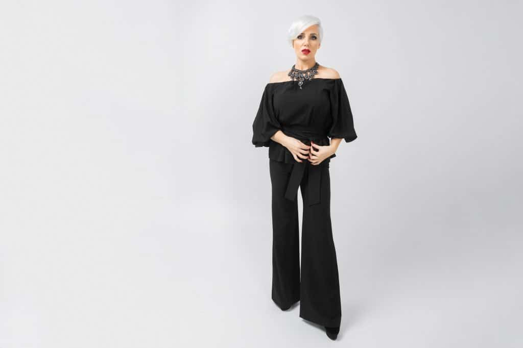 woman in black wide leg pants and off the shoulder top. short cropped hair and bold accessories.  #widelegpants #wideleg #widelegjeans #denim #palazzo #croppedwideleg #womensfashion