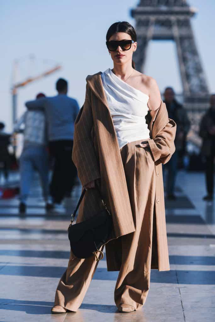 Caucasian woman in Paris in front of Eiffel Tower. Wearing khaki wide leg pants with oversized khaki coat. White one shoulder draped top. Black handbag, black sunglasses. #widelegpants #wideleg #widelegjeans #denim #palazzo #croppedwideleg #womensfashion
