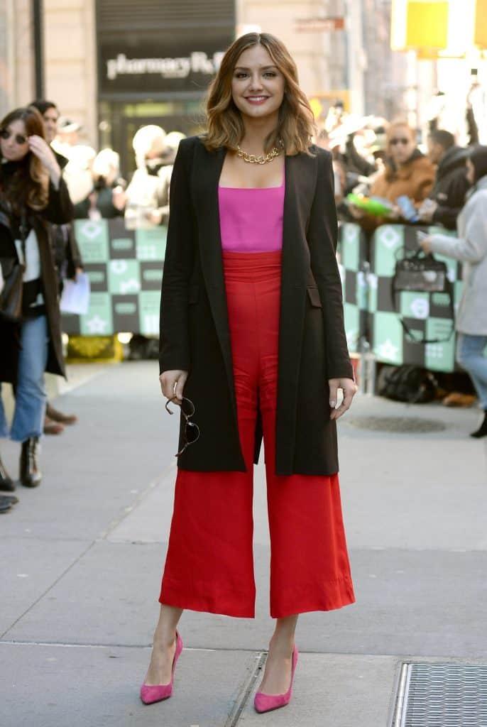 Christina Evangelista wearing red wide leg pants with pink top, long black open front blazer, and red heels. #widelegpants #wideleg #widelegjeans #denim #palazzo #croppedwideleg #womensfashion
