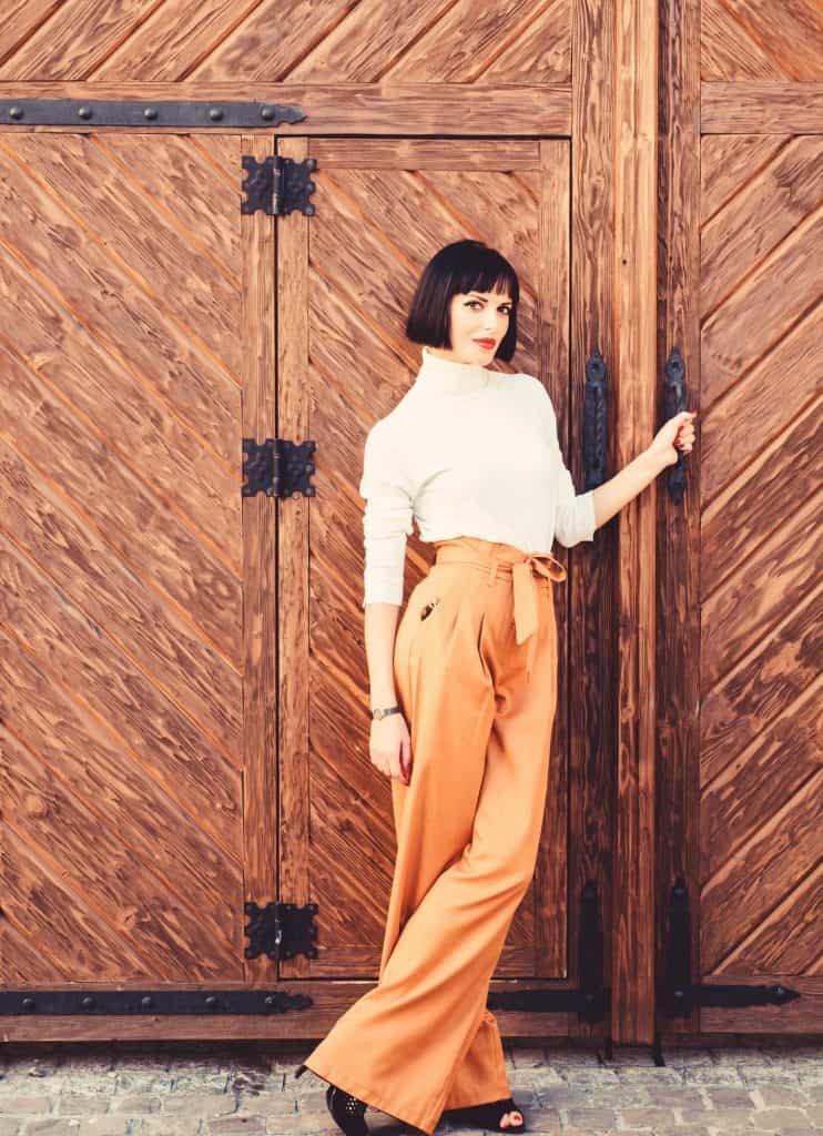 Caucasian woman standing in front of a wooden door. She is wearing orange wide leg paper bag pants, white turtleneck. #widelegpants #wideleg #widelegjeans #denim #palazzo #croppedwideleg #womensfashion