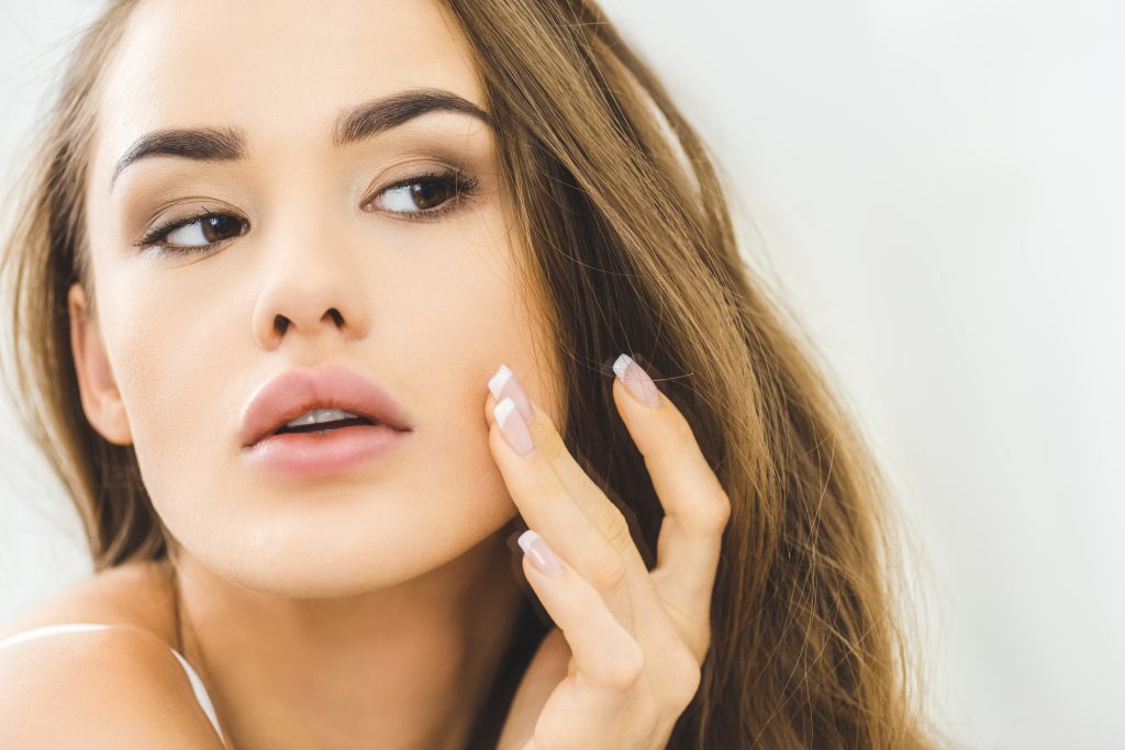 Caucasian woman examining her cheek. Dermaplaning benefits, side effects, and kits to perform dermaplaning at home. #skincare #skincareproducts #skincarereview #dryskin #acneprone #oilyskin