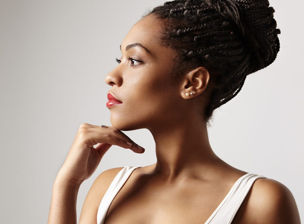 Profile of beautiful black women wearing braids in a bun and with smooth skin. Dermaplaning benefits, side effects, and kits to perform dermaplaning at home. #skincare #skincareproducts #skincarereview #dryskin #acneprone #oilyskin