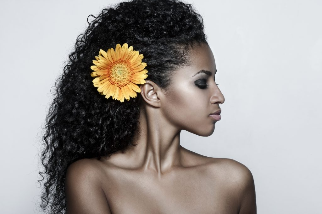 Beautiful dark skinned woman with a sunflower in her hair shoulders up shot. Dermaplaning benefits, side effects, and kits to perform dermaplaning at home. #skincare #skincareproducts #skincarereview #dryskin #acneprone #oilyskin
