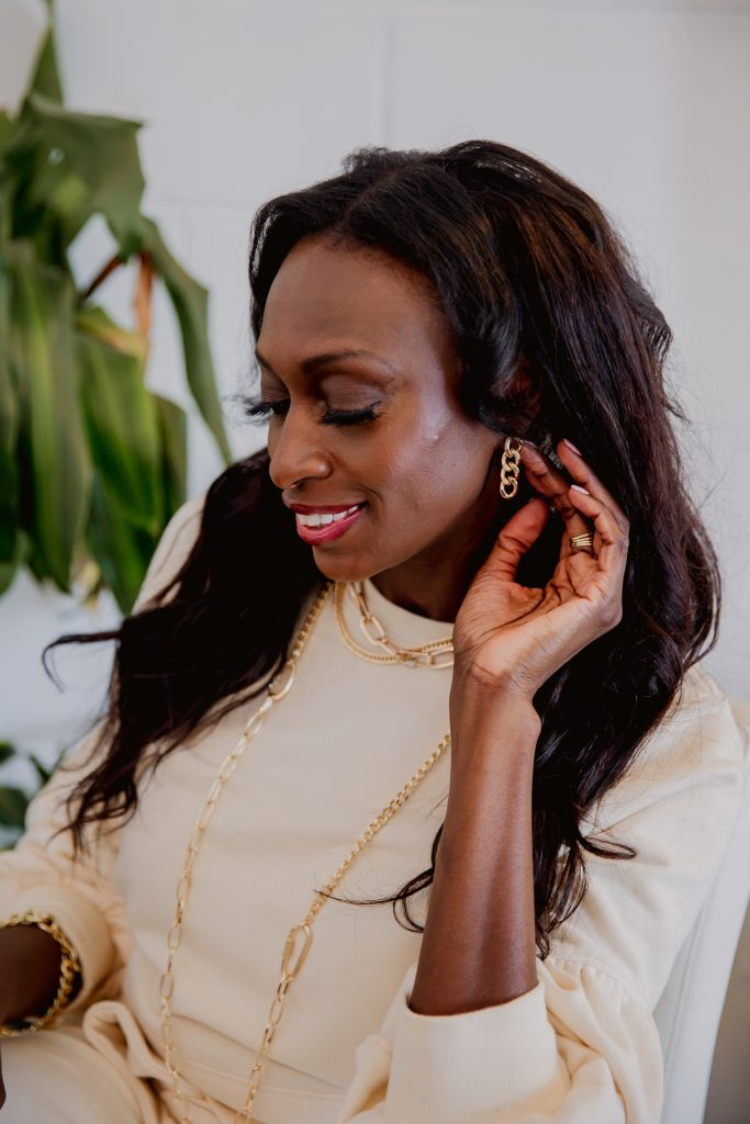 Sitting in white chair next to green plant showing off gold chainlink earrings. also wearing layered chain necklaces of different withs and styles. gold chain bracelet and gold stack ring set. jewelry trends spring summer chains & hardware