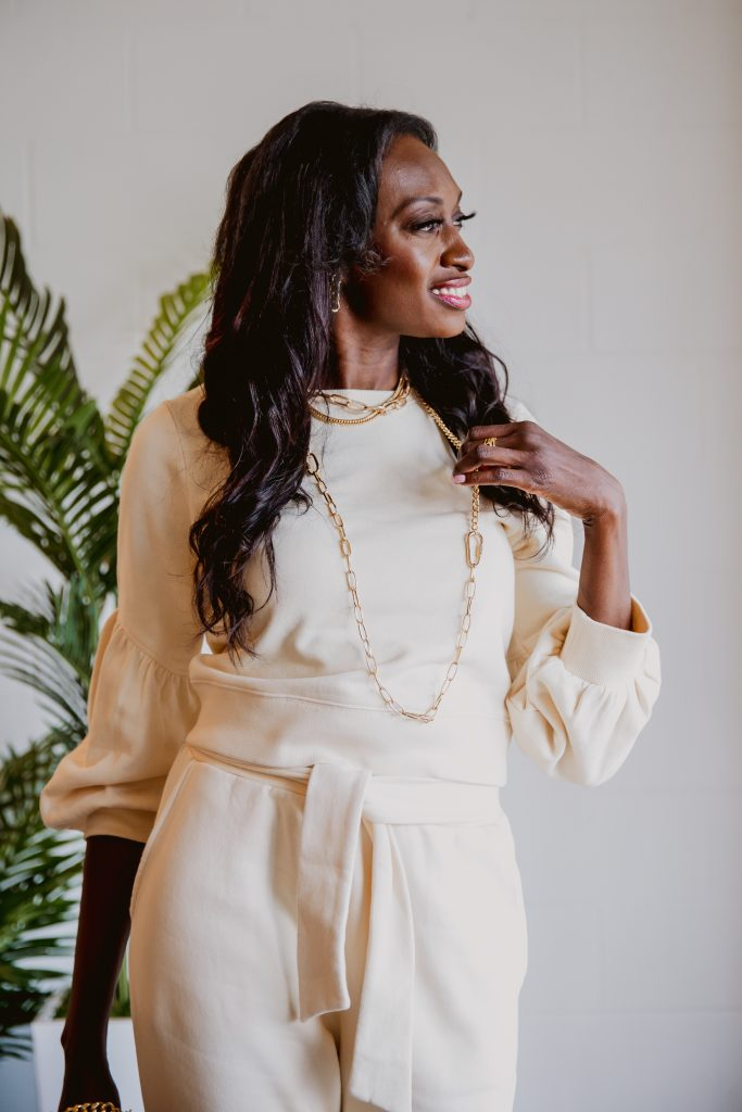 womens jewelry trends spring summer. layer gold chainlink necklaces of differing lengths and widths, add gold chainlink bracelet and gold chainlink earrings. Trendy jewelry paired with creamy yellow sweatsuit.